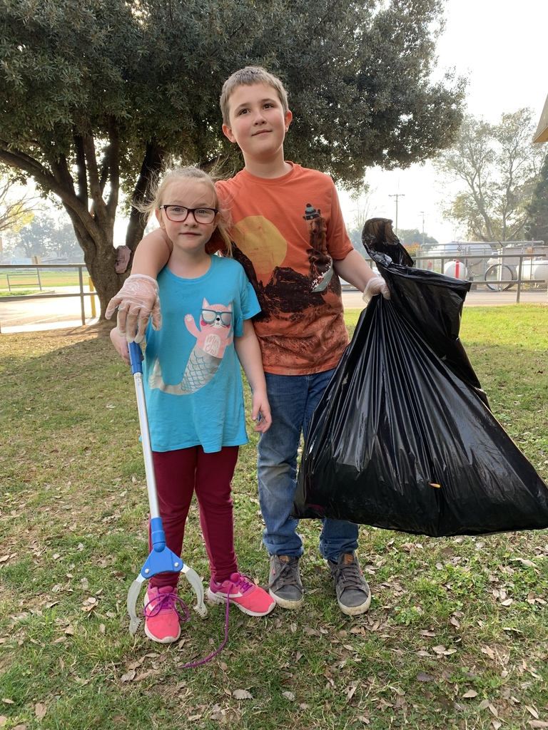 Kids holding garbage bag on front lawn
